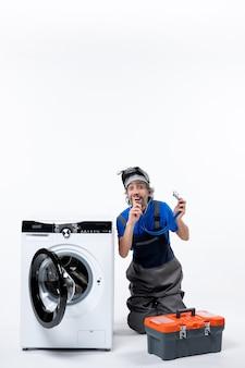 Vorderansicht eines jungen mechanikers, der ein shh-zeichen in der nähe einer waschmaschine an einer weißen wand macht?