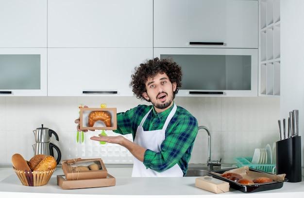 Vorderansicht eines jungen selbstbewussten mannes, der frisch gebackenes gebäck in einer kleinen schachtel in der weißen küche zeigt
