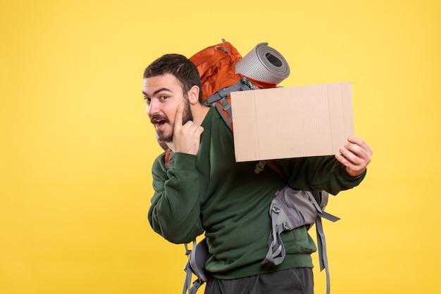 Vorderansicht eines jungen selbstbewussten reisenden kerls mit rucksack und mit einem blatt, ohne auf gelbem hintergrund zu schreiben