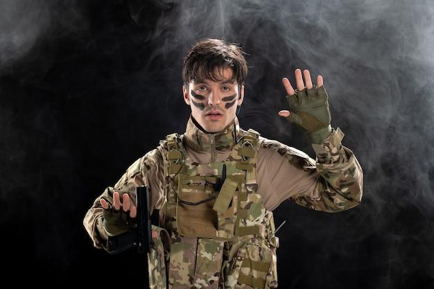Vorderansicht eines jungen soldaten, der sich in uniform auf einer dunklen rauchigen wand ergibt