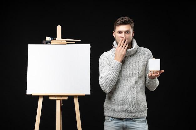 Vorderansicht eines jungen und talentierten männlichen künstlers, der ein pinselminibuch mit überraschtem gesichtsausdruck auf schwarz hält