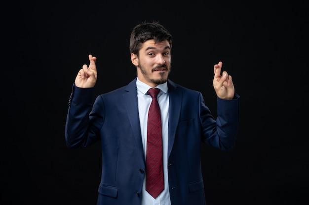 Vorderansicht eines jungen und zufriedenen bärtigen mannes, der seine finger an einer isolierten dunklen wand kreuzt