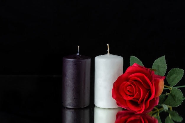 Vorderansicht eines kerzenpaares mit roter rose auf schwarz