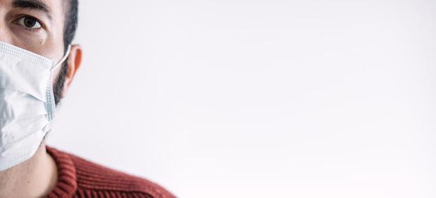 Vorderansicht eines kranken erwachsenen im krankenhaus, der eine schutzmaske trägt, um gegen durch die luft übertragene krankheit zu schützen. konzept der coronavirus-quarantäne. medizinischer patient des bannerpanoramas mit platz für text