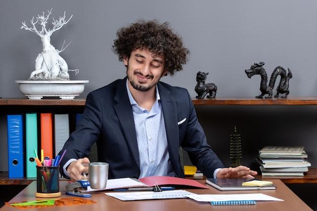 Vorderansicht eines lächelnden geschäftsmannes, der tee am schreibtisch im büro trinkt in