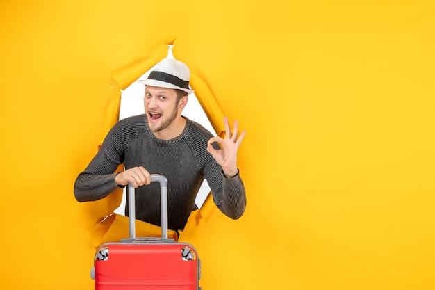 Vorderansicht eines lächelnden jungen mannes mit einem hut, der eine tasche hält und eine brillengeste in einer zerrissenen gelben wand macht