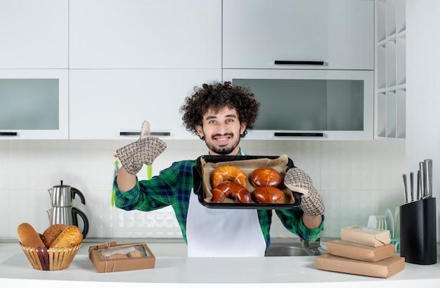 Vorderansicht eines lächelnden jungen mannes mit halter, der frisch gebackenes gebäck zeigt, das in der weißen küche eine gute geste macht