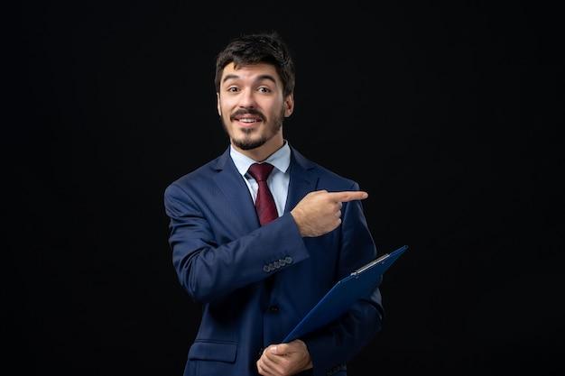 Vorderansicht eines lächelnden männlichen büroangestellten im anzug, der dokumente hält und etwas auf der linken seite auf isolierte dunkle wand zeigt