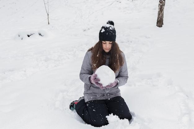 Vorderansicht eines mädchens, das schneeball in der winterlandschaft hält