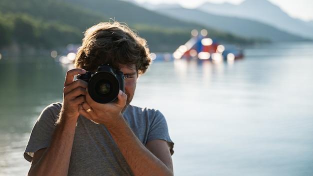 Vorderansicht eines männlichen fotografen, der mit einer digitalkamera bei ruhigem morgenmeer fotografiert