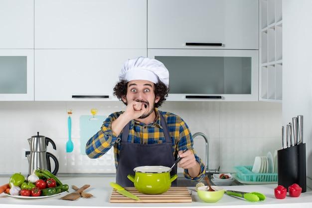 Vorderansicht eines männlichen kochs mit frischem gemüse und einem löffel in der mahlzeit, der sich in der weißen küche verängstigt fühlt