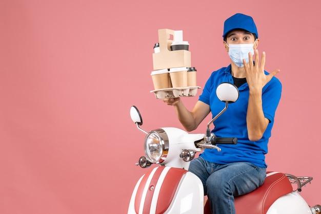 Vorderansicht eines männlichen lieferers in maske mit hut, der auf einem roller sitzt und bestellungen liefert, die zehn auf pfirsichhintergrund zeigen