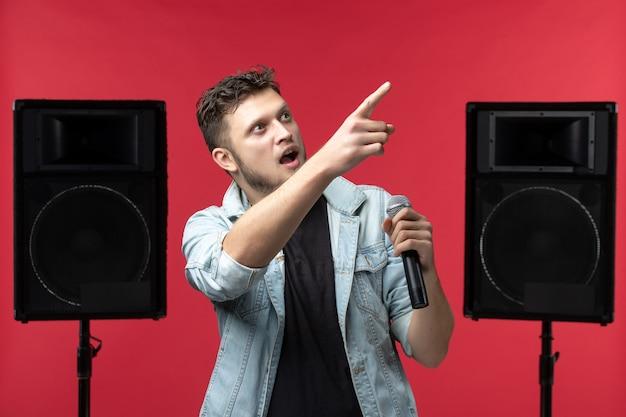 Vorderansicht eines männlichen sängers auf der bühne mit mikrofon an roter wand