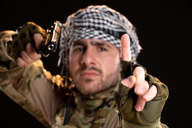 Vorderansicht eines männlichen soldaten in tarnung, der mit einer waffe auf eine schwarze wand zielt