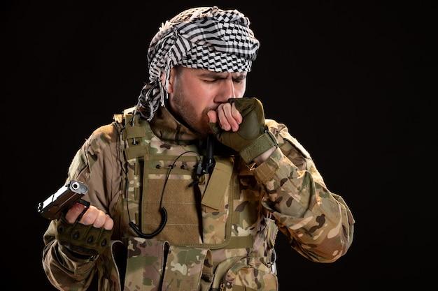 Vorderansicht eines männlichen soldaten in tarnung mit pistole auf schwarzer wand