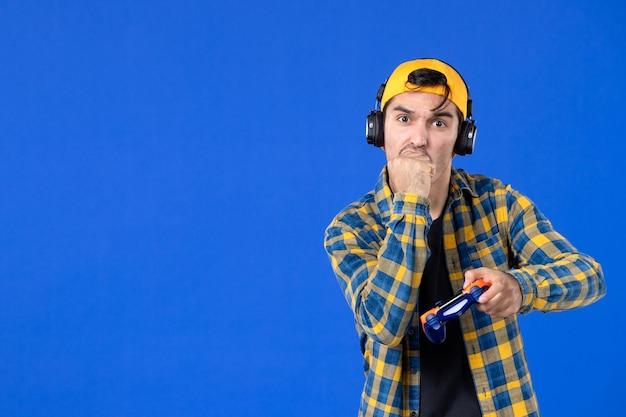 Vorderansicht eines männlichen spielers mit gamepad und kopfhörern, die videospiele an blauer wand spielen