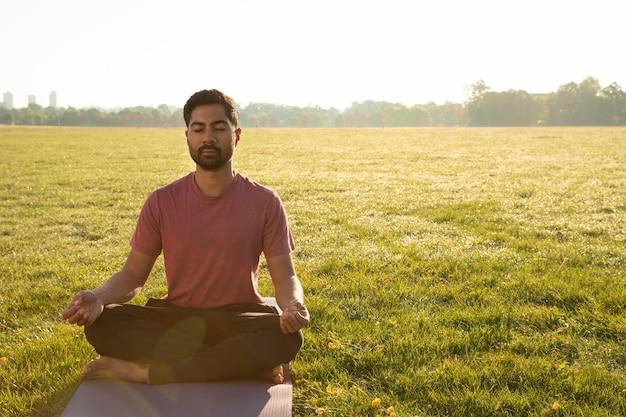 Vorderansicht eines mannes, der draußen auf einer yogamatte meditiert