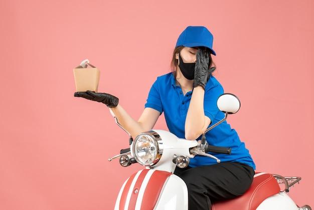 Vorderansicht eines müden lieferers mit medizinischer maske und handschuhen, der auf einem roller sitzt und bestellungen mit kopfschmerzen auf pastellfarbenem pfirsichhintergrund liefert
