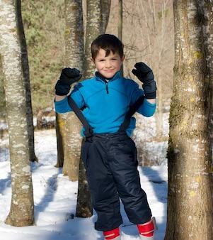 Vorderansicht eines netten jungen, der auf schnee beim schauen der kamera steht