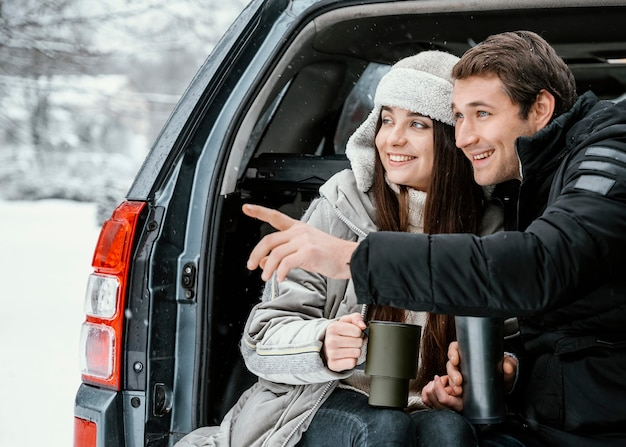 Vorderansicht eines paares, das während eines road trips ein warmes getränk im kofferraum des autos trinkt