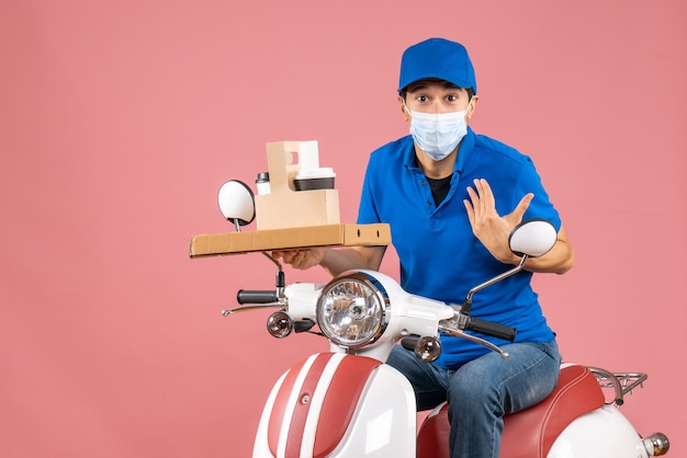 Vorderansicht eines schockierten männlichen lieferers in maske mit hut, der auf einem roller sitzt und bestellungen auf pastellfarbenem pfirsichhintergrund liefert