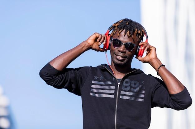 Vorderansicht eines schwarzen mannes, der die zufällige kleidung und sonnenbrille stehen in der straße bei der anwendung von kopfhörern trägt, um musik am sonnigen tag zu hören