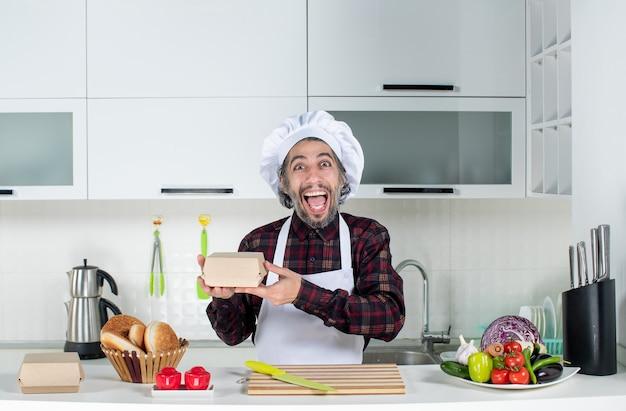 Vorderansicht eines sehr aufgeregten männlichen kochs, der eine kiste in der küche hält