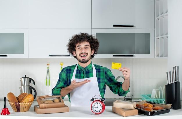 Vorderansicht eines selbstbewussten jungen mannes, der hinter dem tisch steht, verschiedene backwaren darauf und eine bankkarte in der weißen küche hält
