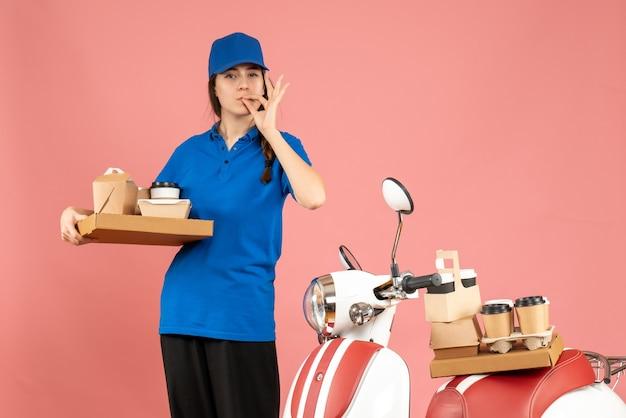 Vorderansicht eines selbstbewussten kuriermädchens, das neben dem motorrad steht und kaffee und kleine kuchen auf pastellfarbenem pfirsichhintergrund hält