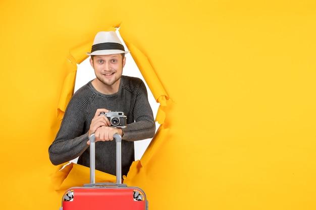 Vorderansicht eines selbstbewussten lächelnden erwachsenen, der tasche und kamera in einer zerrissenen gelben wand hält
