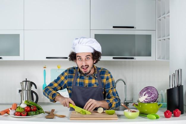 Vorderansicht eines selbstbewussten männlichen kochs mit frischem gemüse, das grüne paprika in der weißen küche hackt