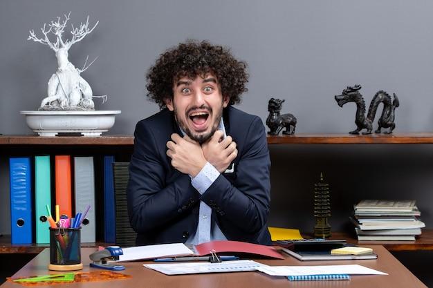 Vorderansicht eines überglücklichen büroangestellten, der im büro am schreibtisch sitzt