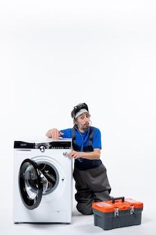 Vorderansicht eines verwunderten mechanikers, der in der nähe der waschmaschine sitzt und seine hand auf die weiße wand hebt