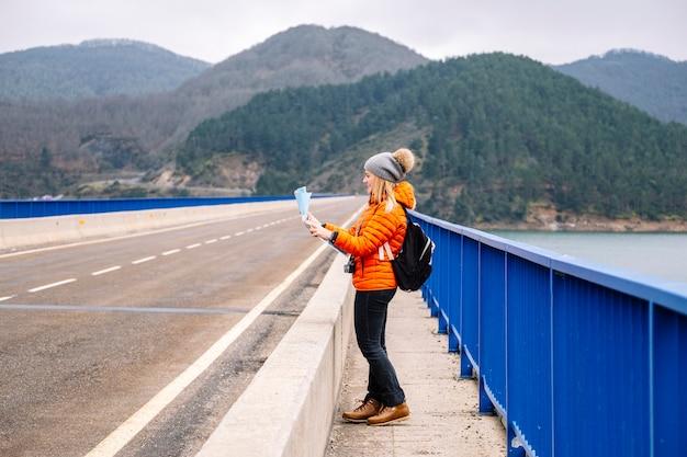 Vorderansicht eines weiblichen touristen mit einer karte, die auf einer straße mit einem grünen berg geht