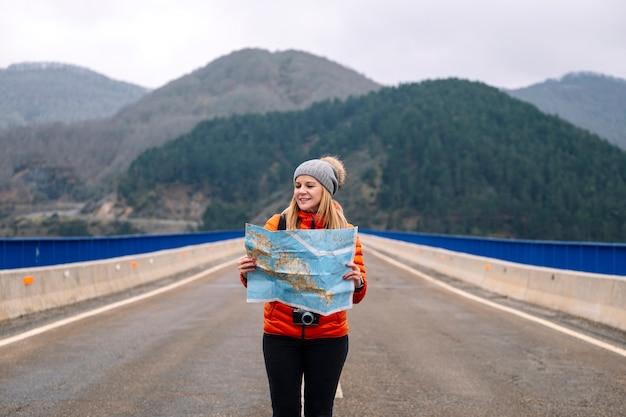 Vorderansicht eines weiblichen touristen mit einer karte, die auf einer straße mit einer grünen berglandschaft dahinter geht