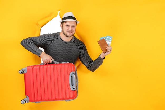 Vorderansicht eines zufriedenen erwachsenen mit tasche und ausländischem reisepass mit ticket in einer zerrissenen gelben wand