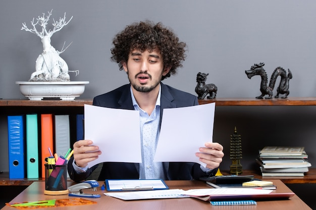 Vorderansicht eines zufriedenen jungen geschäftsmannes, der im büro arbeitet