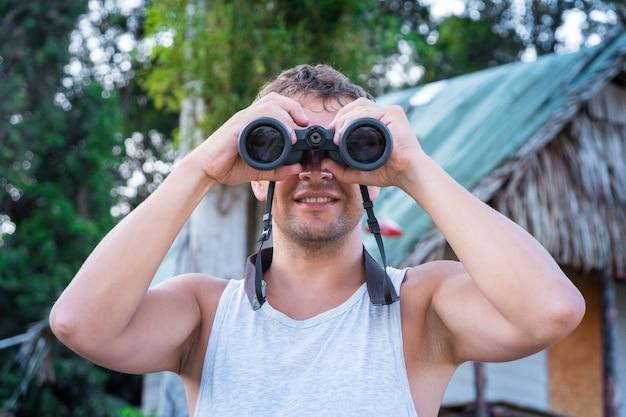 Vorderansicht eines zufriedenen jungen mannes in einem weißen t-shirt schaut durch fernglas vor dem hintergrund einer dorfhütte.