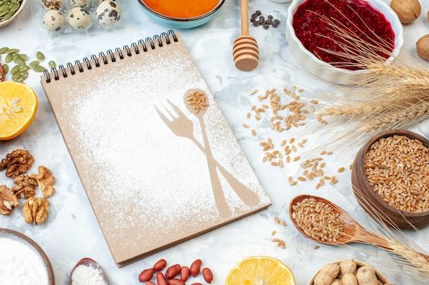 Vorderansicht einfacher notizblock mit mehl-eier-gelee und verschiedenen nüssen auf weißem hintergrund fruchtnuss-zucker-farbkuchen-foto süßer kuchenteig
