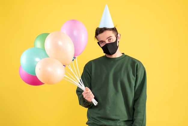Vorderansicht enttäuschter junger mann mit partykappe und bunten luftballons, die auf gelb stehen