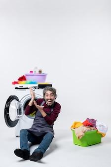 Vorderansicht erfreute männliche haushälterin, die vor waschmaschinenwäschekorb auf weißem hintergrund sitzt