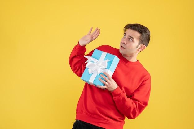 Vorderansicht erschreckte jungen mann mit rotem pullover, der auf gelb steht