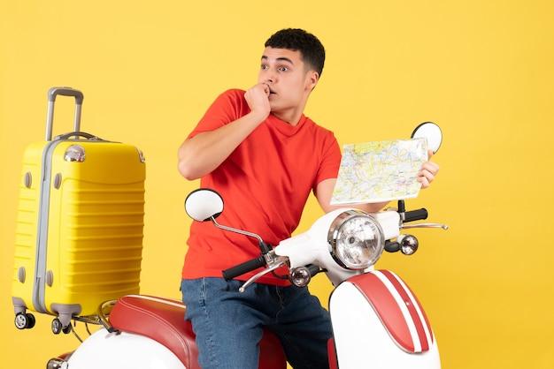 Vorderansicht erschreckter junger mann in der freizeitkleidung auf moped, das karte hält