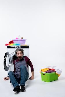 Vorderansicht erschrockener haushältermann, der nahe wäschekorb auf weißer wand sitzt