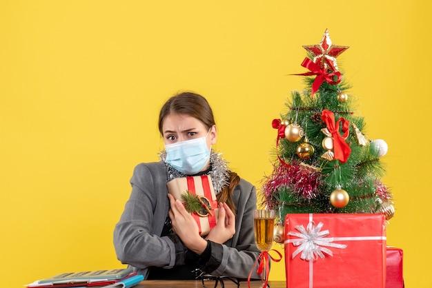 Vorderansicht erschrockenes mädchen mit medizinischer maske, die ihren geschenkweihnachtsbaum und geschenkcocktail hält