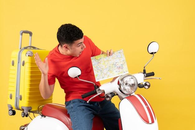 Vorderansicht erstaunte gutaussehender mann auf moped, das karte hält