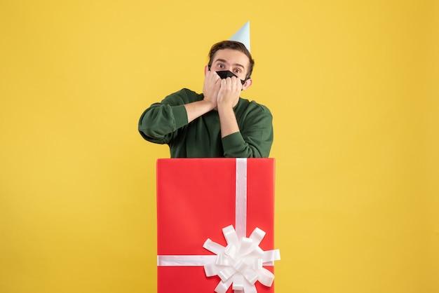 Vorderansicht erstaunte jungen mann mit partykappe, die hinter großer geschenkbox auf gelb steht