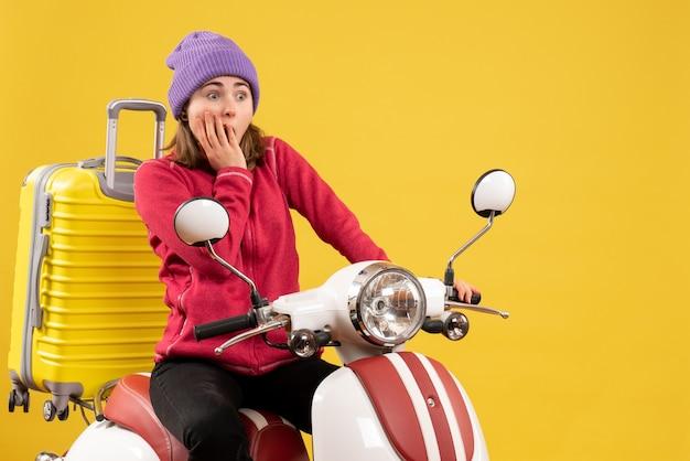 Vorderansicht erstaunte junges mädchen auf moped, das auf etwas starrte