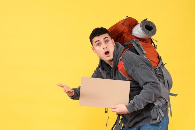 Vorderansicht erstaunter junger mann mit rotem rucksack, der pappe hält