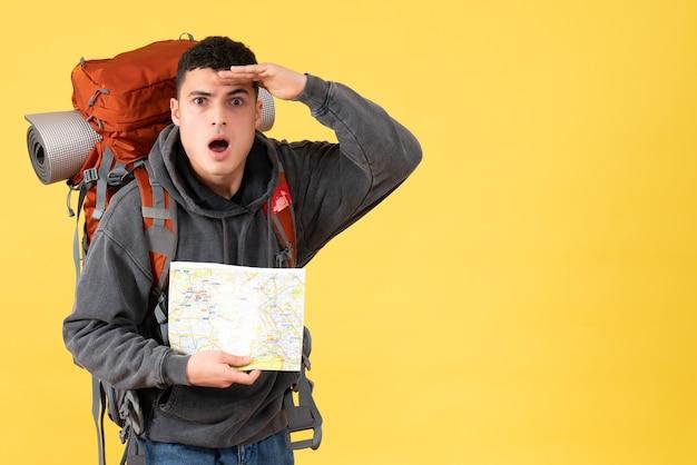 Vorderansicht erstaunter reisender mann mit rucksack, der karte hält